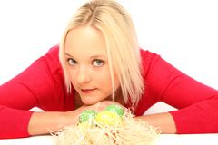 Blond woman with easter eggs. Beautiful blond woman laying on the floor with some easter eggs royalty free stock photos