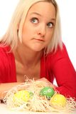 Blond woman with easter eggs. Beautiful blond woman laying on the floor with some easter eggs royalty free stock photo