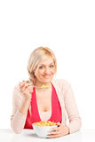 Blond woman eating cereal from a bowl Royalty Free Stock Photo