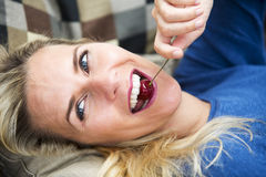 Blond woman eating a cherry. Portrait of blond woman lying on couch and eating cherries Stock Image