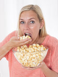 Blond woman eating popcorn Royalty Free Stock Photography
