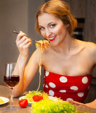Blond woman eating spaghetti in the kitchen at home Stock Images