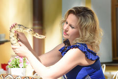 Blond woman in elegant dress with a python Royalty Free Stock Photography
