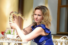 Blond woman in elegant dress with a python Royalty Free Stock Photo