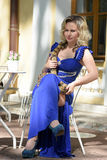 Blond woman in elegant dress with a python Stock Photography