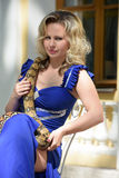Blond woman in elegant dress with a python Stock Images