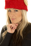 Blond woman elf hat close look hand under chin. A woman with an elf hat on, in a black shirt with a serious expression Royalty Free Stock Image