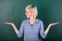 Blond Woman With Empty Palms Against Chalkboard Royalty Free Stock Image