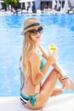 Blond woman enjoying cocktail near the swimming pool Stock Photography