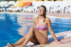 Blond  woman enjoying the summer vacation laying on sunbed in a tropical garden Stock Image