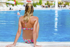 Blond  woman enjoying the summer vacation laying on sunbed in a tropical garden Stock Photography