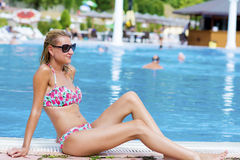 Blond  woman enjoying the summer vacation laying on sunbed in a tropical garden Stock Photo