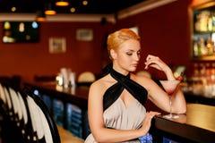 Blond woman in evening dress. Beautiful blond woman in evening dress sitting near bar counter Royalty Free Stock Photos