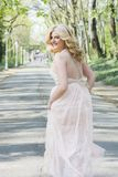 Blond woman in evening gown running Stock Photo