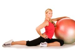 Blond woman exercising with a pilates ball. On the white background Royalty Free Stock Images
