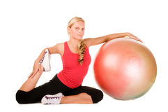 Blond woman exercising with a pilates ball. Over white background Stock Photography
