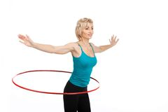 Blond woman exercising using hoop. Aged lady standing hands aside on white background Royalty Free Stock Photography