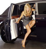 Blond woman exiting a luxury car Stock Photos