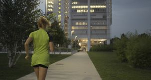 Blond woman in fitness wear running training on park walkway.Back following view.Summer evening or night.Industrial