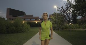 Blond woman in fitness wear running training on park walkway.Front following view.Summer evening or night.Industrial