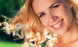 Blond woman, flipping curly hair. Sunny summer nature. Stock Images