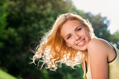 Blond woman, flipping curly hair. Sunny summer nature. Close up of blond woman with curly hair flipping them in the air in yellow singlet in green nature. Sunny Stock Image