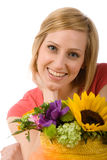 Blond Woman with Flowers. Close-up portrait of a beautiful, blue-eyed, blond woman with colorful flowers in the foreground Royalty Free Stock Image