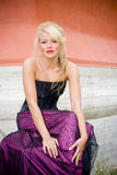 Blond woman in formal dress. A view of a pretty blond woman as she sits and poses in a long, formal dress against a painted brick wall Stock Photos