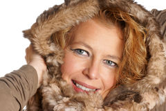 Blond woman with fur hood. Studio shot of a smiling blond woman with blue eyes wearing a fur hood over a white background Royalty Free Stock Photography
