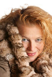 Blond woman with fur hood. Studio shot of a smiling blond woman with blue eyes wearing a fur hood over a white background Stock Images