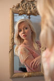 Blond Woman Gazing at Self in Mirror. A portrait of a young woman looking at her reflection in a fancy mirror Royalty Free Stock Images