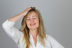 Woman happy gesture. A woman got a brilliant idea which brings relief; neutral background Royalty Free Stock Images