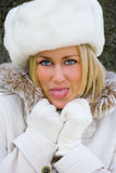 Blond Woman Girl White Fur Hat, Coat Sticking Out her Tongue Royalty Free Stock Photography