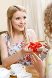 Blond woman giving gift in cafe Stock Images