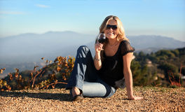 Blond woman with a glass of wine. Blond woman enjoying wine at the winery Stock Photo