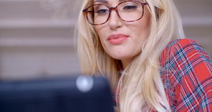Blond Woman with Glasses Busy with Tablet Computer stock video