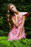 Blond woman in green bush. In pink dress Stock Photography