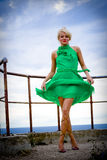 Blond woman in green dress. A beautiful blond woman wearing green dress, posing at a sea or ocean Royalty Free Stock Image