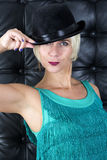 Blond woman in green dress with black hat Royalty Free Stock Images