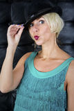 Blond woman in green dress with black hat Stock Images