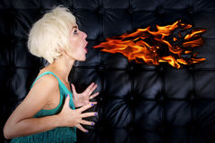 Blond woman in green dress spitting fire Stock Images