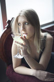 Blond Woman in Green Top Drinking a Martini. Photo of a very attractive blonde outside driniking a margarita from a martini glass Royalty Free Stock Images