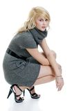 Blond woman with grey dress squatting Royalty Free Stock Photography