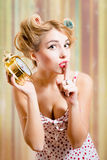Blond woman with haircurlers dotted langerie. Close up portrait of showing silence sign amazing young blond pinup woman with haircurlers in her hair in dotted Stock Images