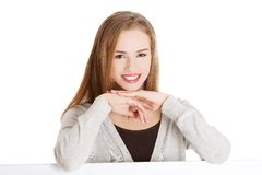 Blond woman with hand on chin sitting at the desk Stock Images