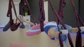 The blond hair woman hangs on the hammock during the personal training in the gym. The blond woman hangs on the hammock during the personal training in the gym stock video