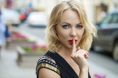 Blond Woman has put forefinger to lips as sign of silence. Young beautiful blonde woman has put forefinger to lips as sign of silence, outdoors royalty free stock photography