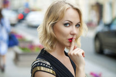 Blond Woman has put forefinger to lips as sign of silence Stock Photography