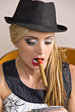 Blond woman with hat, cigar. Beautiful young blond woman wearing black hat holding playing cards with cigar in mouth Royalty Free Stock Photo