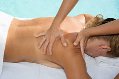 Blond woman having a shoulder massage in a spa center Stock Image